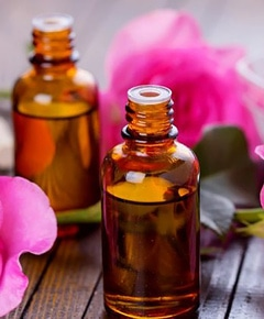 essential aroma oil with roses on wooden background how to make essential oils ss feature 750x420
