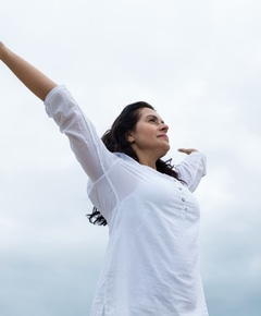 Happy woman standing with arms outstretched 8pxat9r